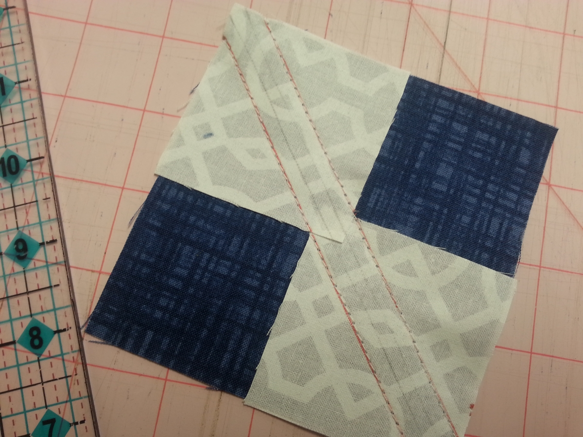 "1 large blue square with 2 smaller squares at opposite corners.  Draw a line 1/4"" from the middle."